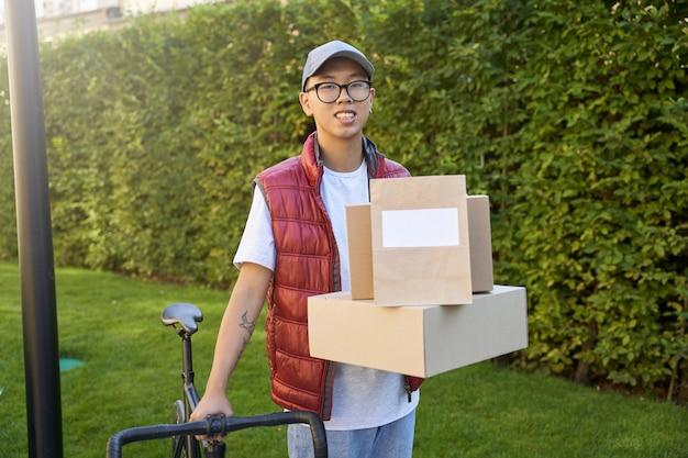 Jonge aziatische mannelijke koerier met pakketten en papieren zakken en dozen voor levering en kijken