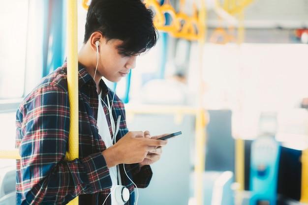 Jonge aziatische mannelijke passagier die mobiele telefoon op openbare bus met behulp van.