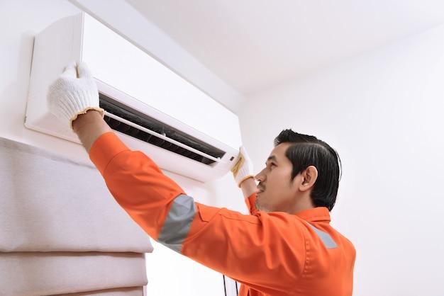 Jonge aziatische mannelijke technicus die airconditioner herstelt