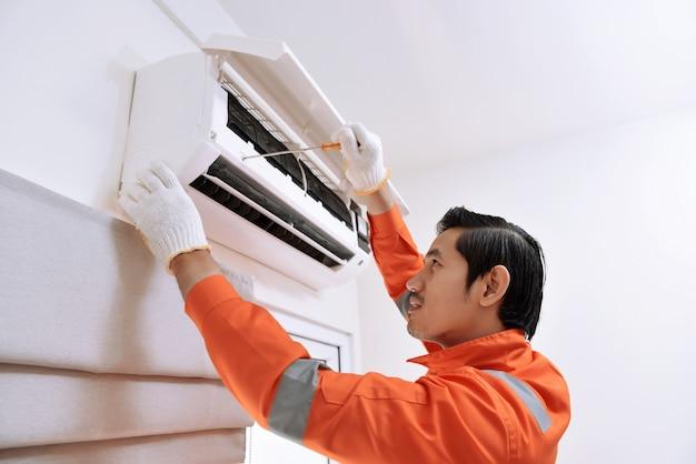 Jonge aziatische mannelijke technicus die airconditioner met schroevedraaier herstelt