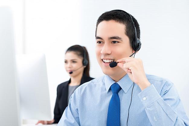 Jonge aziatische mannelijke telemarketing klantenserviceagent die in call centre werkt