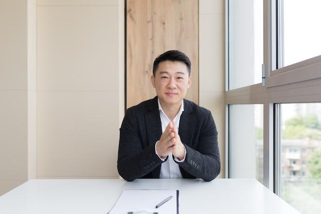 Jonge aziatische mannelijke zakenman die online praat tijdens een videogesprek, conferentie of vergadering die naar de camera kijkt. webcamweergave. azië man in pak binnenshuis. kantoor onderhandelingen afstand overleg of advies