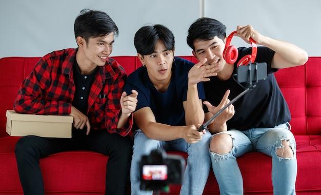 Jonge aziatische mannen gebruiken smartphone om beoordeling van moderne hoofdtelefoons op te nemen voor technologievlog terwijl ze thuis op de bank zitten