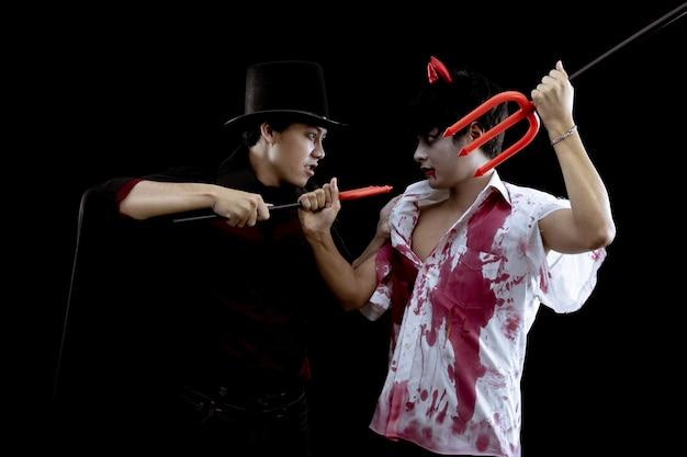 Jonge aziatische mannen in kostuum hel, kwaad en tovenaar met strijd op zwarte muur met concept voor halloween-modefestival. twee tiener aziatische man in cosplay halloween.