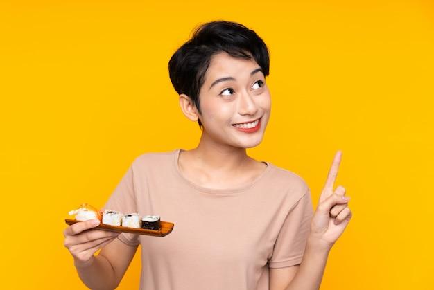 Jonge aziatische meisje met sushi van plan om de oplossing te realiseren terwijl ze een vinger opheft