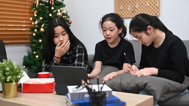 Jonge aziatische meisjes die samen thuis online studeren.