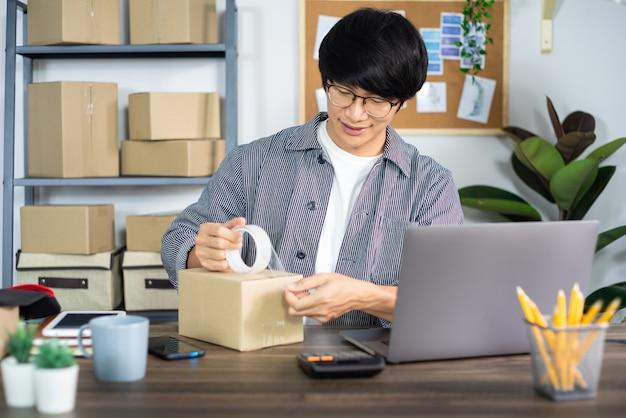 Jonge aziatische mens die aan het bureau van de leveringsdienst werken