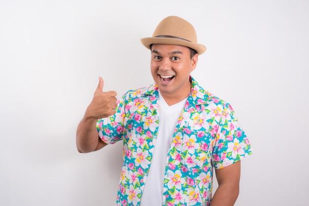 Jonge aziatische mens die de zomeroverhemd dragen en duim voor songkran-festival in thailand tonen.