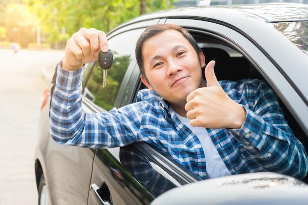 Jonge aziatische mens die duim toont en hand die zijn sleutel in de auto houdt. concept van huurauto of auto kopen.