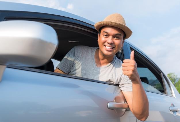 Jonge aziatische mens die duim toont terwijl het drijven van auto.