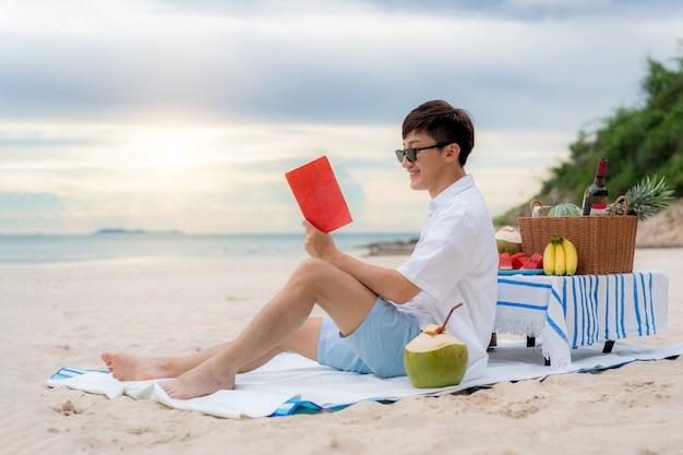 Jonge aziatische mens die een boek op het strand leest
