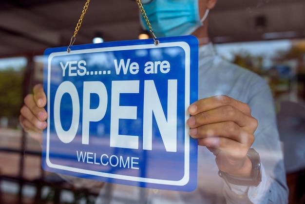 Jonge aziatische mens die een medisch masker draagt en een teken houdt om zijn eigen winkel te openen.