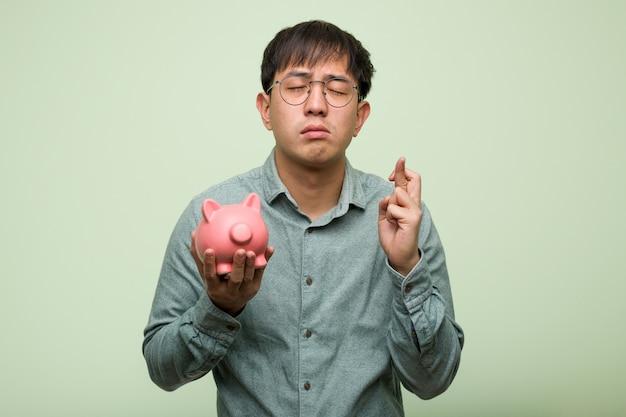 Jonge aziatische mens die een spaarvarken houden die vingers kruisen voor het hebben van geluk