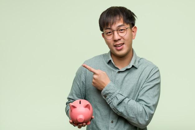 Jonge aziatische mens die een spaarvarken houdt richtend aan de kant met vinger