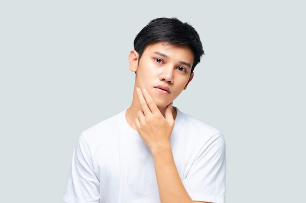 Jonge aziatische mens die een witte t-shirt draagt die zijn hand gebruikt die zijn gezicht controleert
