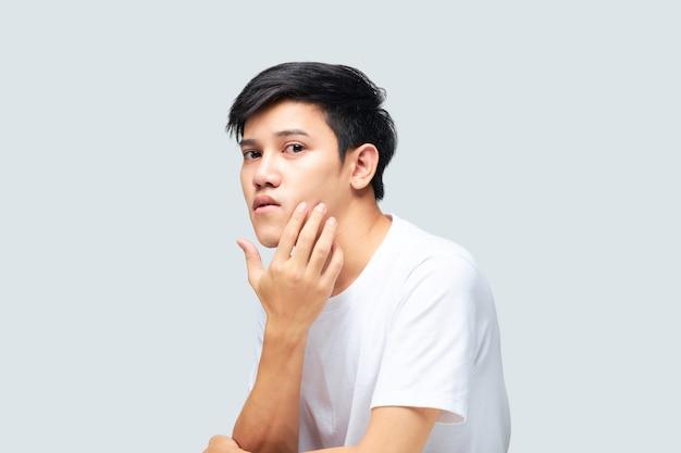 Jonge aziatische mens die een witte t-shirt draagt die zijn hand gebruikt om zijn gezicht te controleren