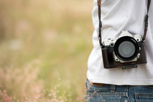 Jonge aziatische mens die foto in openlucht met digitale camera dslr neemt. jonge vrolijke vrouwelijke toerist die pret in koffiewinkel hebben. lifestyle portret concept.