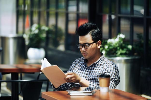 Jonge aziatische mens die in glazen bij openluchtkoffie zitten en boek lezen