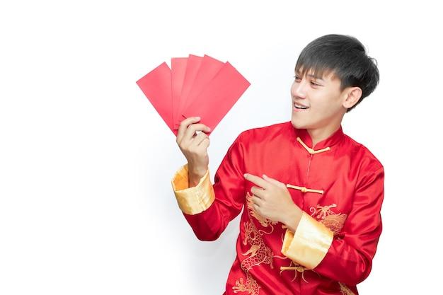 Jonge aziatische mens die in mandarijnkraagkleding rood enveloppakket houdt. chinees nieuwjaar concept.