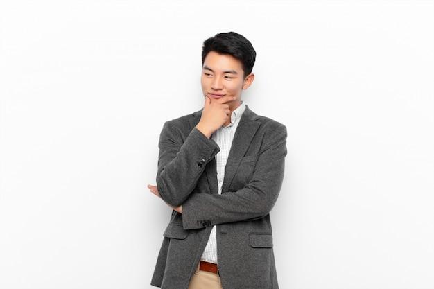 Jonge aziatische mens die met een gelukkige, zekere uitdrukking met hand op kin glimlachen, en aan de kant over kleurenmuur benieuwd zijn kijken