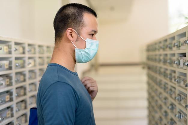 Jonge aziatische mens die met masker de brievenbus controleert