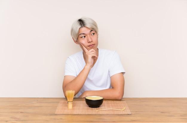 Jonge aziatische mens die met matchathee in een lijst een idee denkt