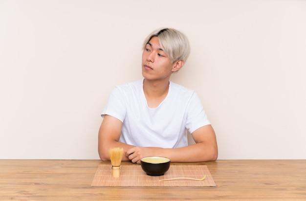 Jonge aziatische mens die met matchathee in een lijst kant kijken
