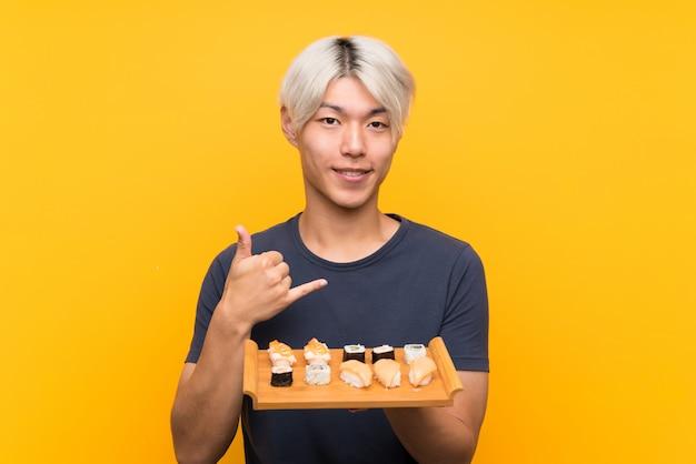 Jonge aziatische mens die met sushi over geïsoleerde gele achtergrond telefoongebaar maken