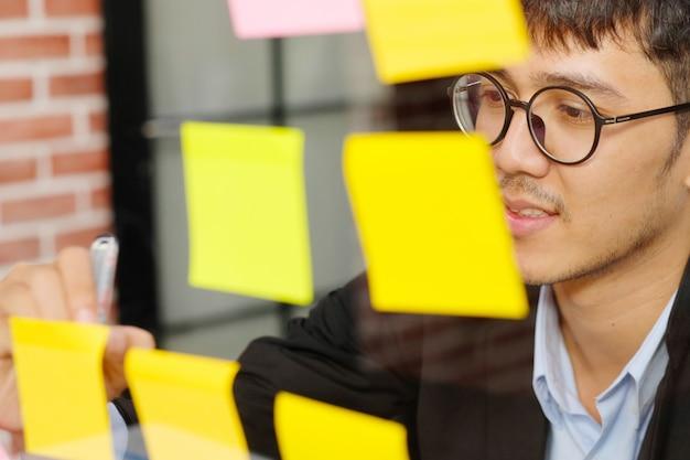 Jonge aziatische mens die op kleverige nota op kantoor, bedrijfsbrainstorming creatieve ideeën, bureaulevensstijl, succes in bedrijfsconcept schrijven