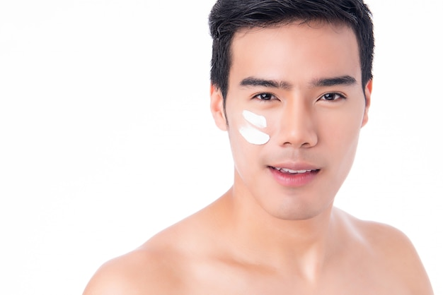 Jonge aziatische mens die roomlotion op gezicht op wit toepast