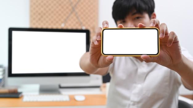 Jonge aziatische mens die slimme telefoon met het lege scherm toont.