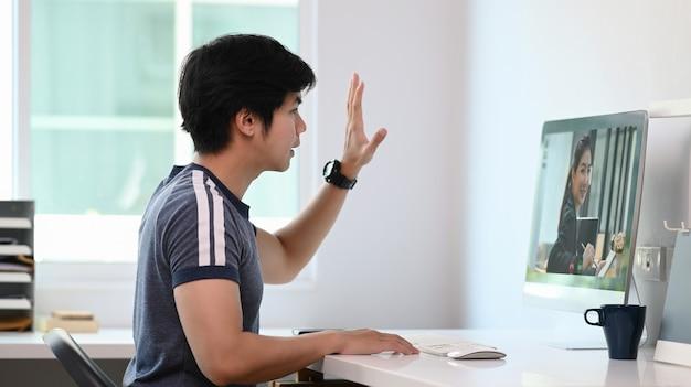 Jonge aziatische mens die videogesprek met zijn zakenpartner op computer maakt.
