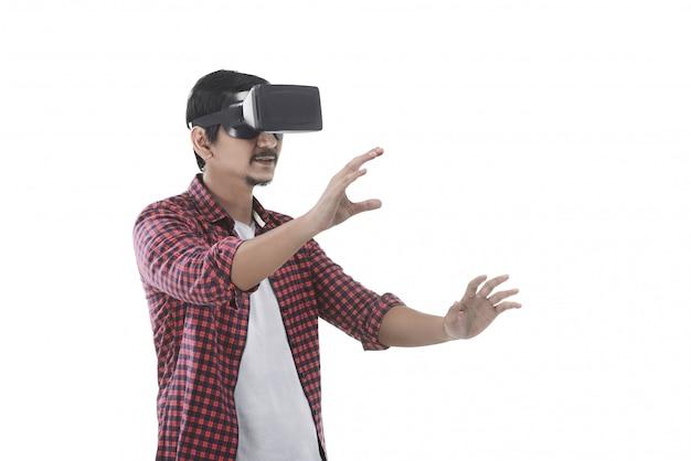 Jonge aziatische mens die virtuele werkelijkheid ervaart door een vr-hoofdtelefoon