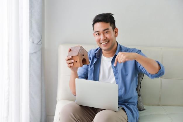 Jonge aziatische mens in blauw overhemd met laptop computer en weinig huismodel die voor banklening tonen voor huisconcept in woonkamer
