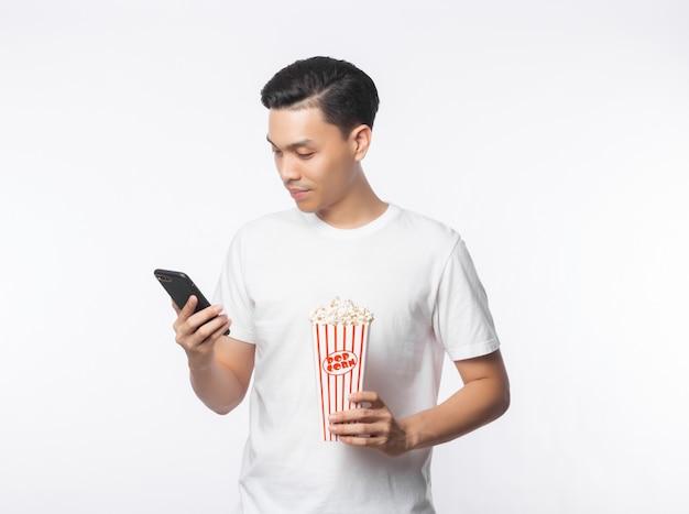 Jonge aziatische mens in witte t-shirt die telefoon kijken en popcorn met gelukkig gezicht houden dat op witte muur wordt geïsoleerd