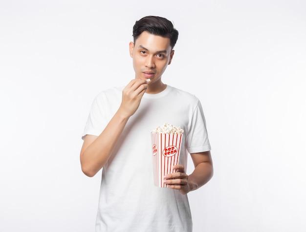 Jonge aziatische mens in witte t-shirtholding en het eten van popcorn met gelukkig geïsoleerd gezicht