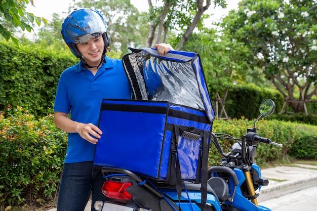 Jonge aziatische mens met leveringsdoos, motorfiets die concept van de voedsel het uitdrukkelijke dienst leveren.