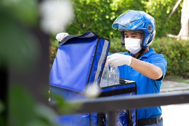 Jonge aziatische mens met leveringsdoos motorfiets die het concept van de voedselexpresdienst levert