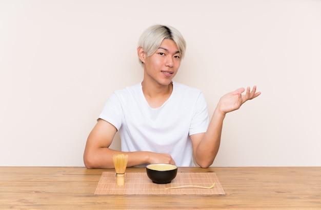 Jonge aziatische mens met matchathee in een lijst die copyspace denkbeeldig op de palm houden