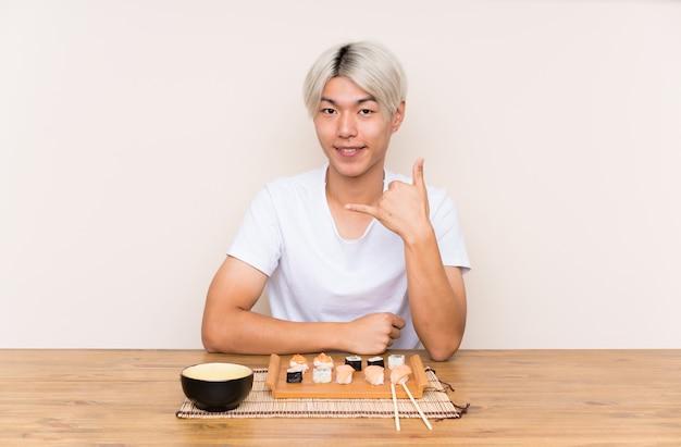 Jonge aziatische mens met sushi in een lijst die telefoongebaar maakt
