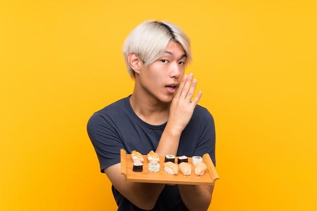 Jonge aziatische mens met sushi over geïsoleerd geel fluisterend iets