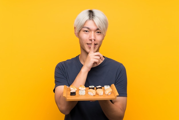 Jonge aziatische mens met sushi over geïsoleerd geel het doen stiltegebaar