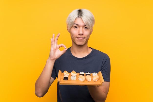Jonge aziatische mens met sushi over geïsoleerde geel tonend een ok teken met vingers