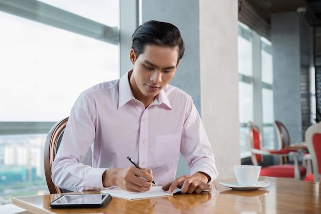 Jonge aziatische mens schrijven in cafe