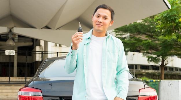 Jonge aziatische mensenhand die zijn sleutel in de auto houdt. concept van huurauto of auto kopen.