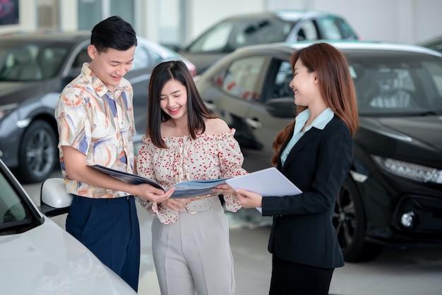 Jonge aziatische minnaars kopen graag een nieuwe auto bij de dealer en kopen een auto bij de autodealer.