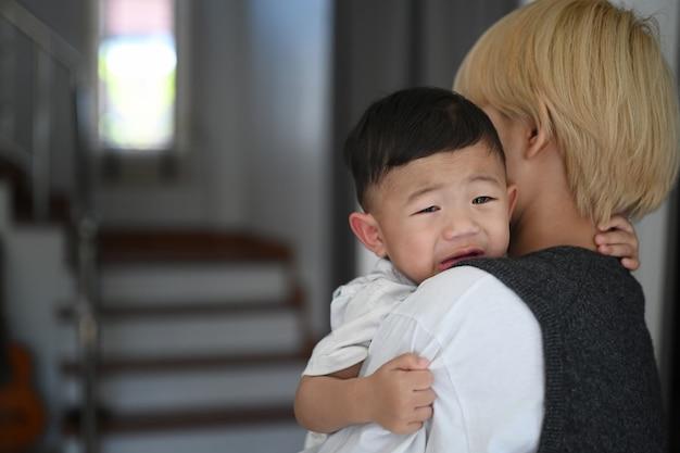 Jonge aziatische moeder die een kalmerende huilende baby vasthoudt in een comfortabel huis.