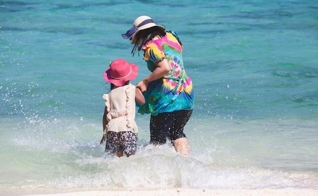 Jonge aziatische moeder en schattige kleine dochter spelen water samen in de prachtige zee
