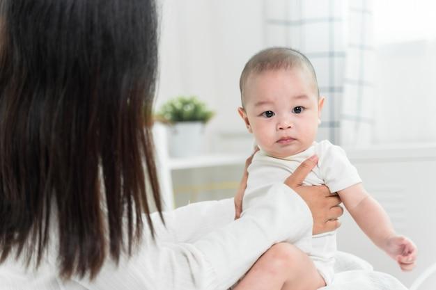 Jonge aziatische moeder met aziatische baby op bed en samen het spelen