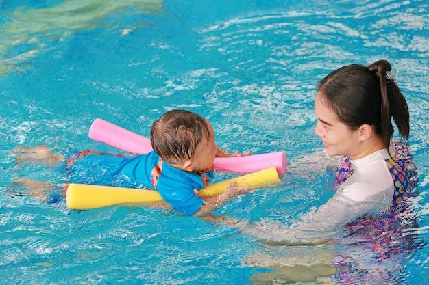 Jonge aziatische moeder onderwijs babyjongen in zwembad met noodle schuim.
